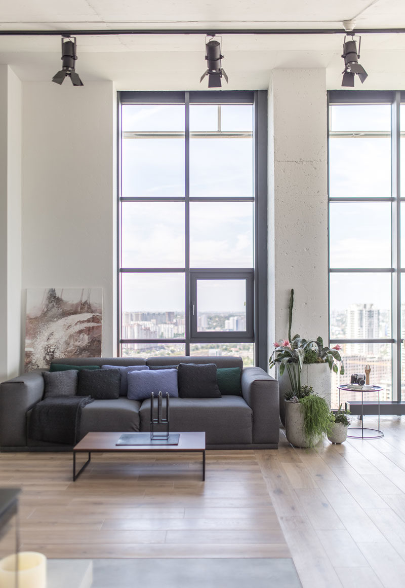 Tall ceilings and metal window frames are featured throughout the apartment that has an industrial modern theme. #ModernIndustrial #LivingRoom #InteriorDesign #Windows