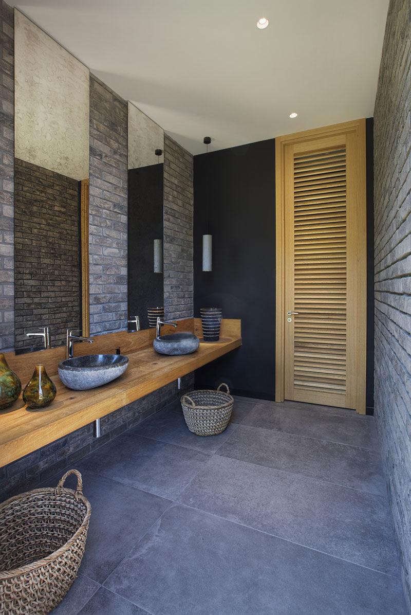 This bathroom has brick walls, a long wood vanity, and tall mirrors that meet the ceiling. #BathroomDesign #ModernBathroom