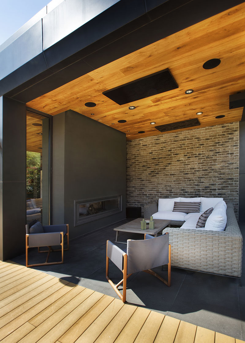This modern poolhouse has a covered outdoor lounge with a wood ceiling, a brick wall, and a double-sided fireplace for cool days. #Poolhouse #OutdoorLivingRoom