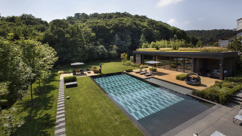 This modern poolhouse, which has a green roof, hasbeen designed to accommodate a living space, kitchenette, outdoor lounge, gym, changing room and toilet. #Poolhouse #SwimmingPool #GreenRoof #Architecture #Landscaping