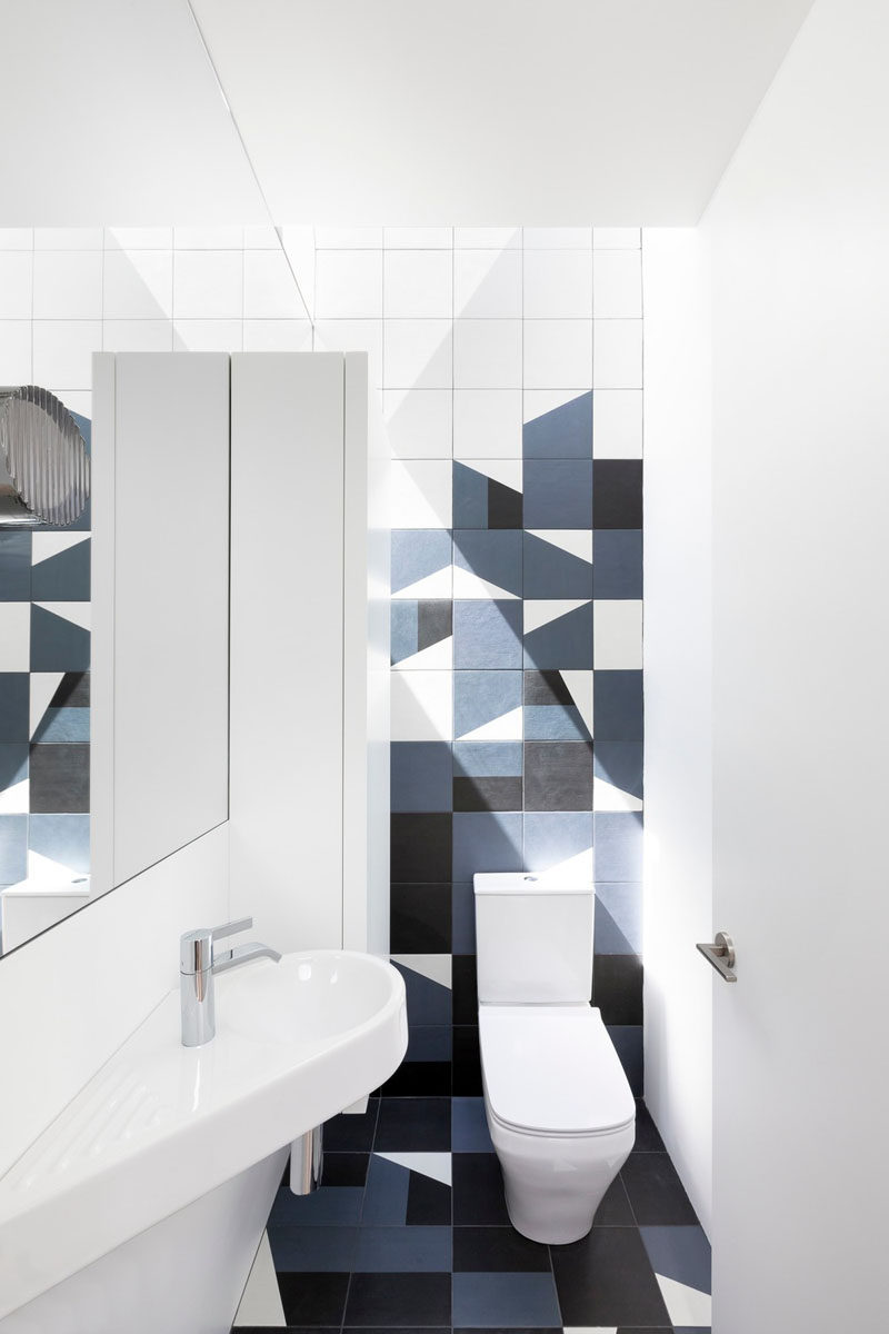 This modern powder room has bold geometric tiles in blue and black.. #ModernBathroom #PowderRoom
