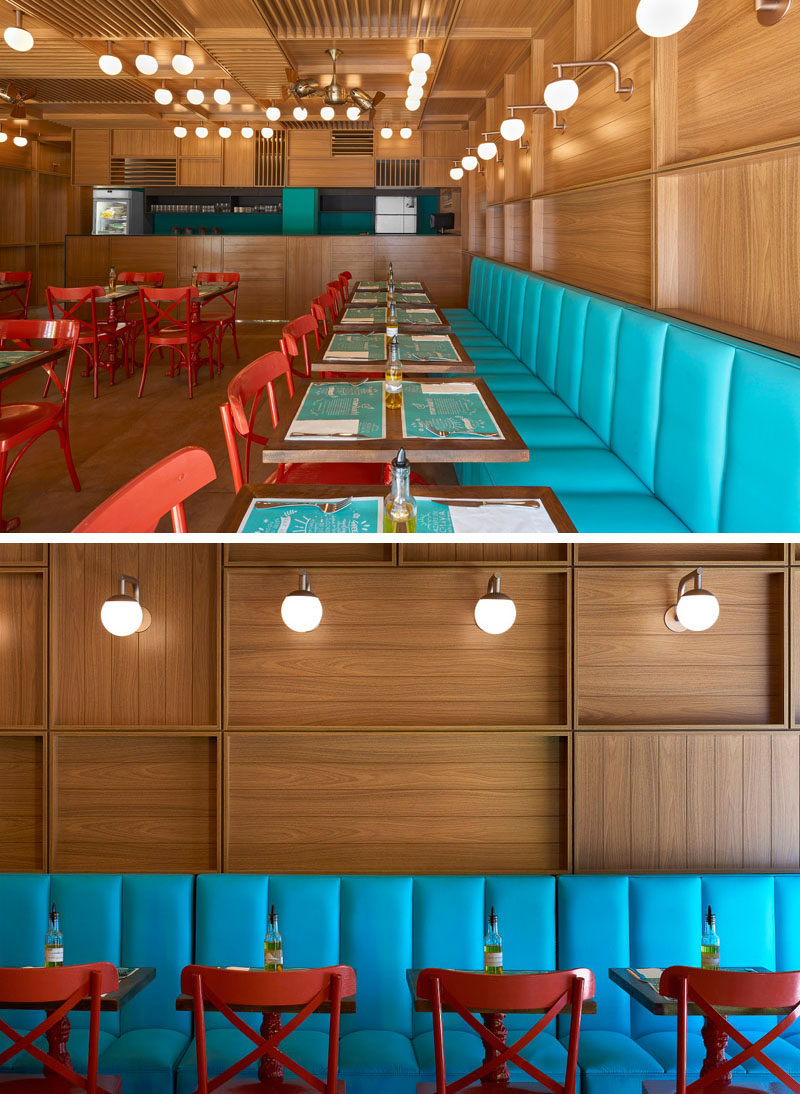 To add some color to the mostly wood interior of this modern restaurant, bright blue banquette seating runs along one wall. #RestaurantDesign #ModernRestaurant