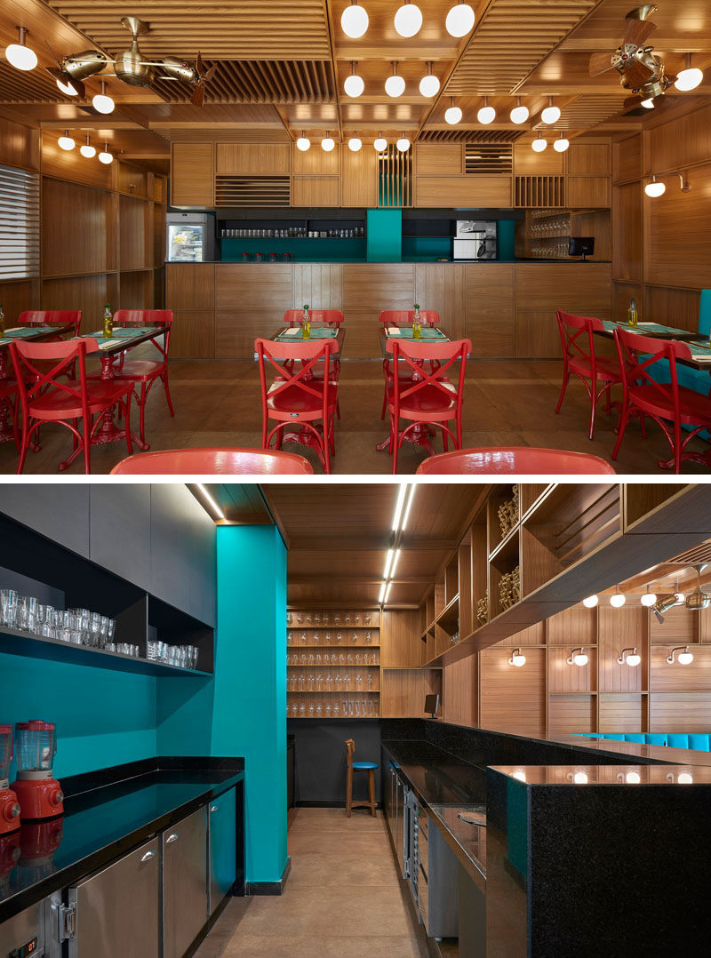 The service area of this modern restaurant has a blue accent wall to match the banquette seating, and black counters complement the black upper cabinets. #RestaurantDesign #ModernRestaurant