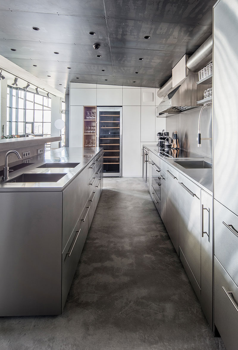 This modern kitchen features concrete flooring, a built-in wine fridge, and stainless steel cabinetry thatcomplements the steel ceiling.