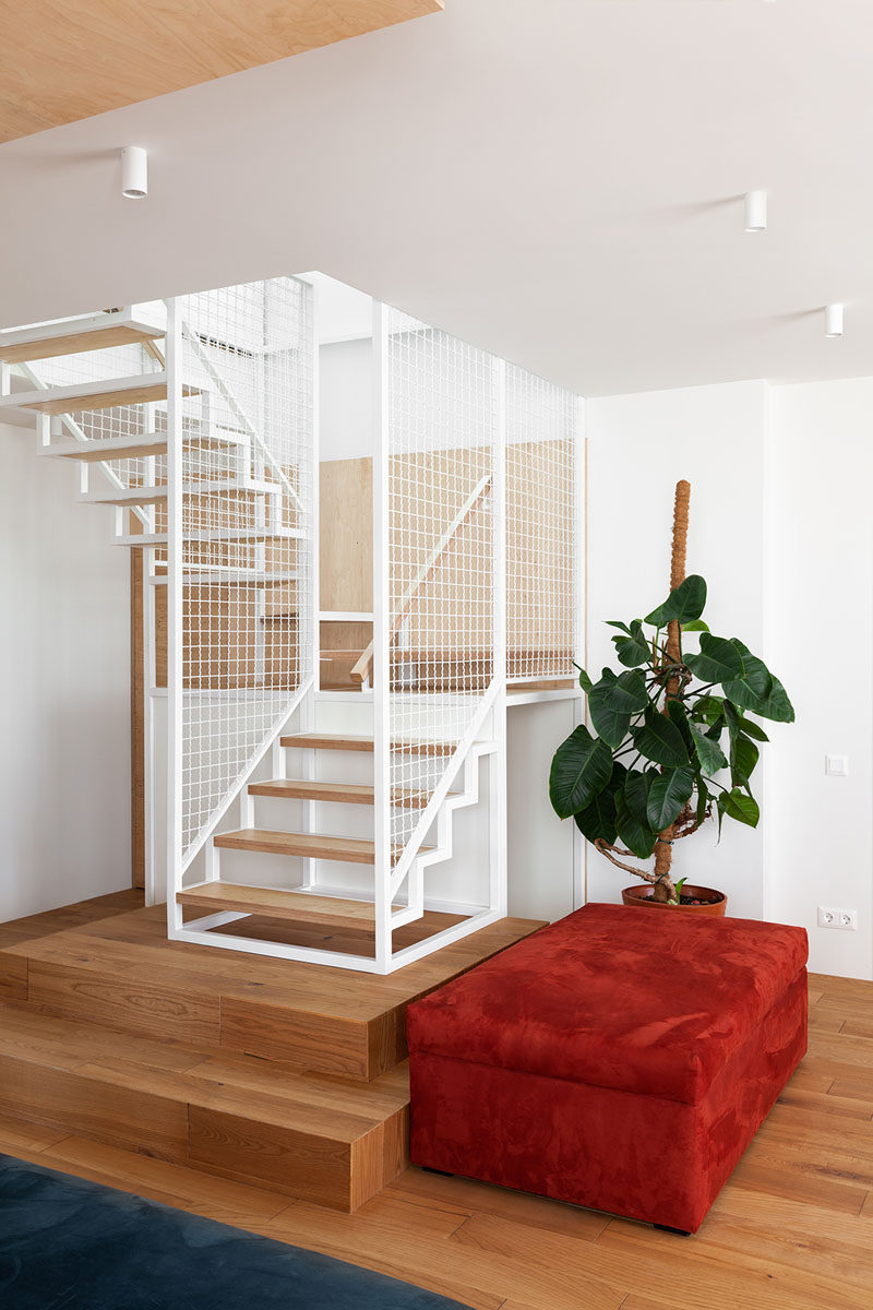 In this modern apartment, white and wood stairs located in the corner of the living room lead to the private areas upstairs. #Stairs #StairDesign