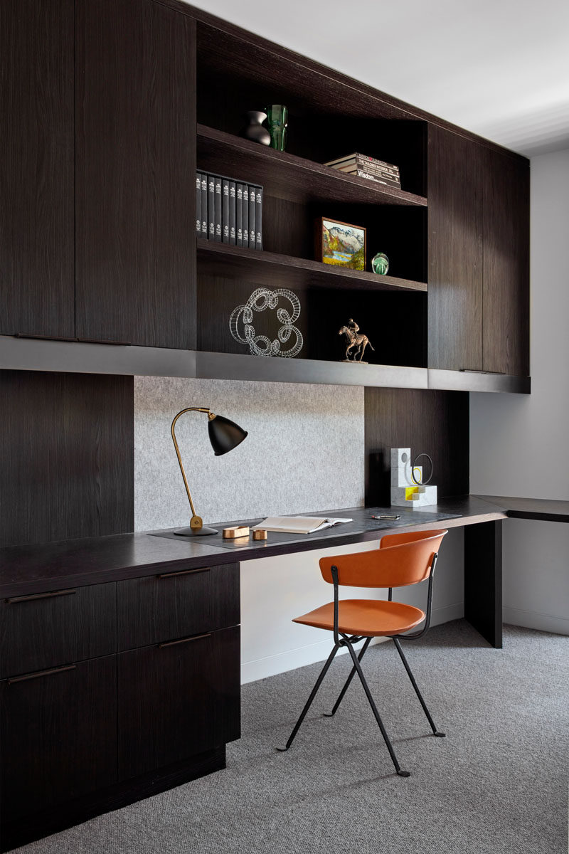 In this modern home office, dark cabinets with open shelving contrast the white walls, while the orange and black chair adds a pop of color. #HomeOffice #ModernHomeOffice #DarkCabinetry