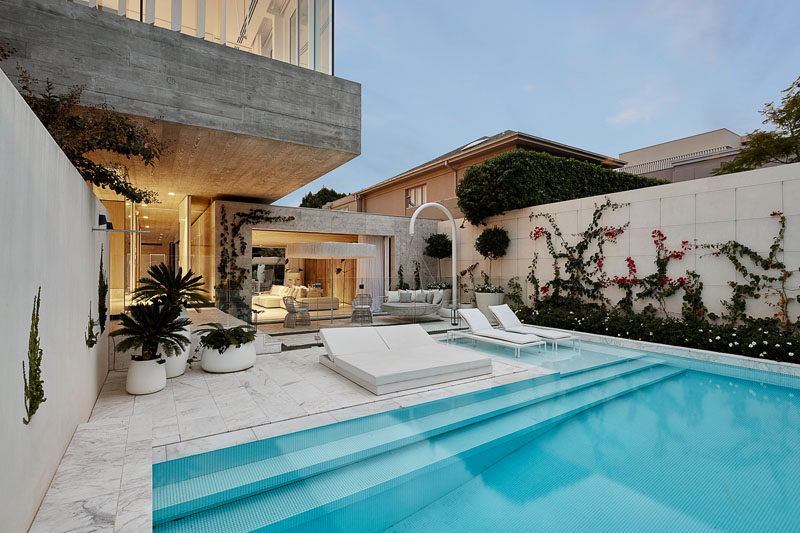 This modern house has a swimming pool that's surrounded by marble tiling. The use of outdoor greenery and an all white colour palate gives the outdoor space the impression of an exotic oasis located within an inner-city environment. #ModernSwimingPool #OutdoorSpace