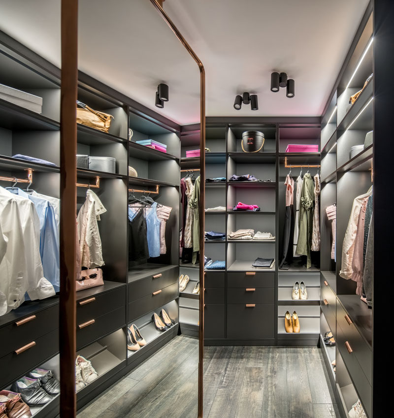 This modern walk-in closet has custom shelving with lighting that fills the walls, and a large mirror. #WalkInCloset #InteriorDesign #Storage
