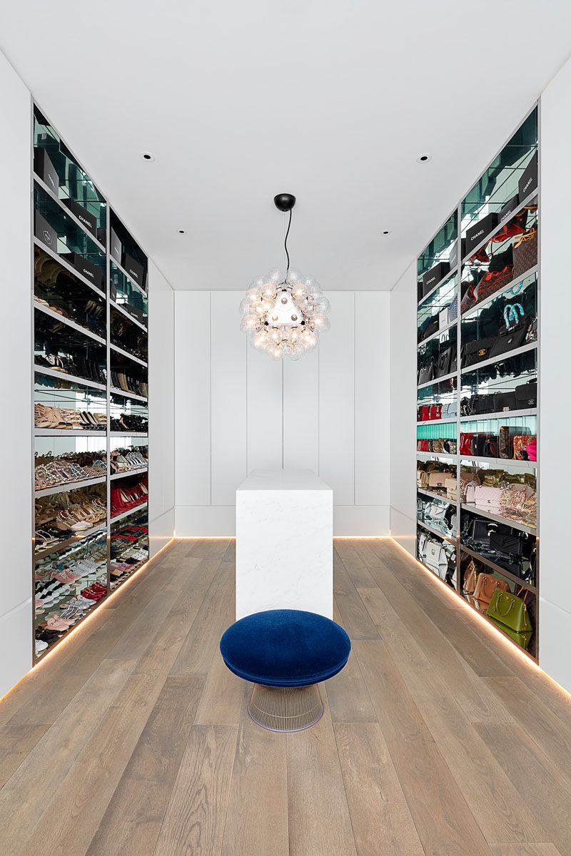 In this modern walk-in closet, the walls are lined with open shelves that have mirrored interiors, while a central island provides additional storage for accessories and smaller items. #WalkInCloset #DressingRoom #InteriorDesign