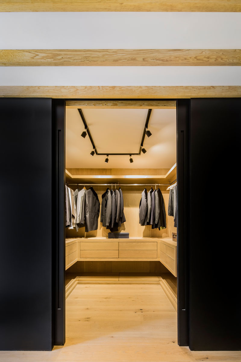 Hidden behind sliding black doors is a walk-in closet, that once opened, reveals a warm wood interior and plenty of storage for clothes. #WalkInCloset #InteriorDesign