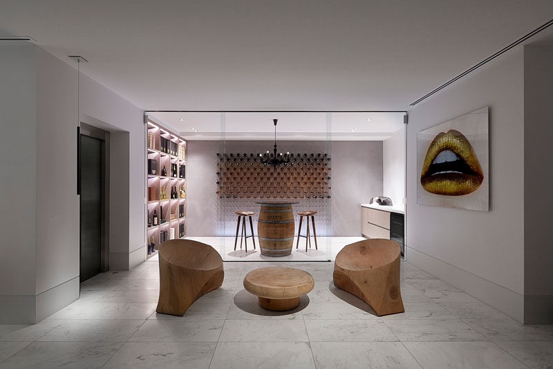 This modern house has a wine cellar that's partitioned by a floor-to-ceiling glass wall. Hidden lighting creates a showroom-like atmosphere, while a couple of sculptural wood chairs provide a quiet place to enjoy a glass of wine. #ModernWineCellar #WineStorage