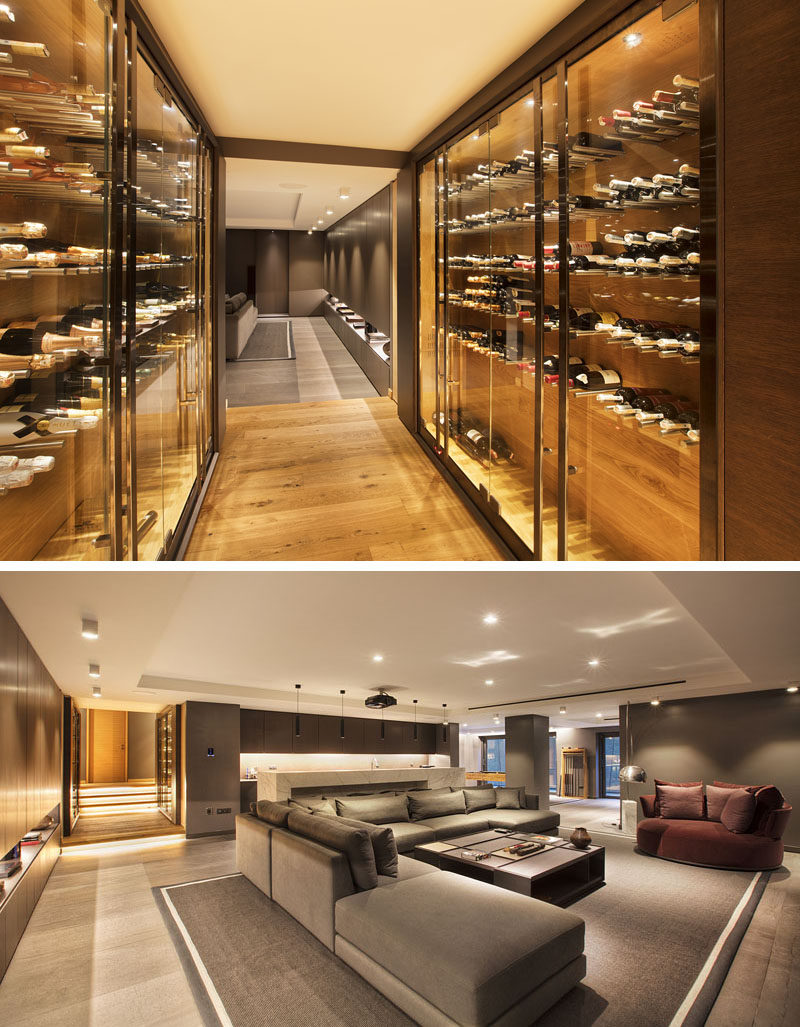 This modern hallway with built-in wine storage, opens up to a family room furnished with a large couch, a bar, and a games area. #WineStorage #FamilyRoom #InteriorDesign