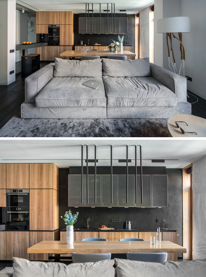 In this modern apartment, the kitchen and the living room were combined into an open space, which is separated by a light grey couch. #ModernKitchen #ModernApartment #ModernInteriorDesign