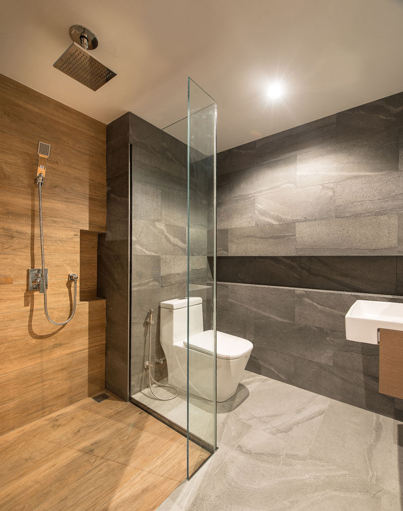 This modern bathroom uses a mixture of grey tiles, wood, and glass, to create a calm experience. #ModernBathroom #BathroomDesign