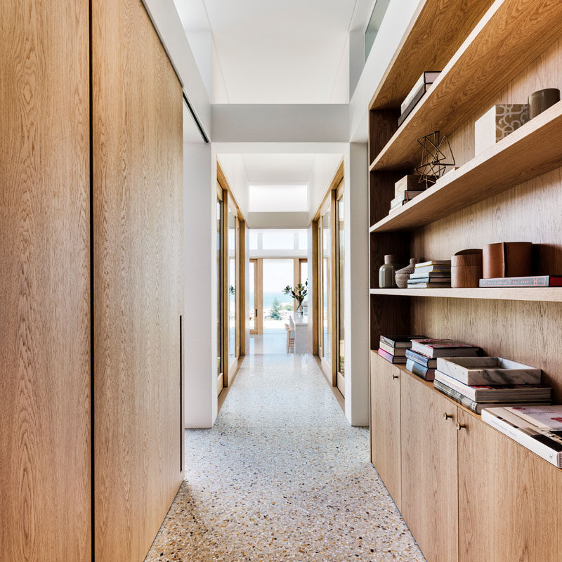 This modern house has a hallway with wood elements, like a bookshelf and door frames, that leads from the front of the house to the living area and kitchen. #ModernHallway #WoodShelving
