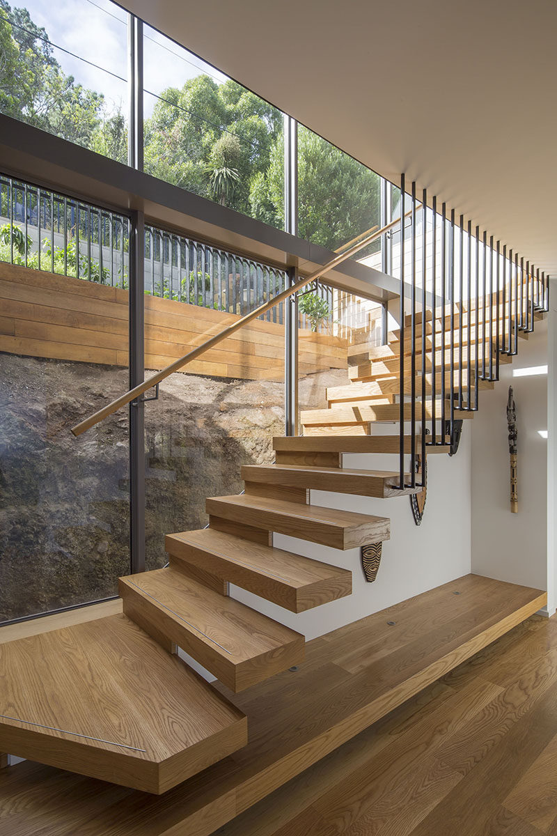 Connecting the various levels of this modern house are cantilevered wood stairs that have a view of the natural rock face. #WoodStairs #Cantilever #StairDesign