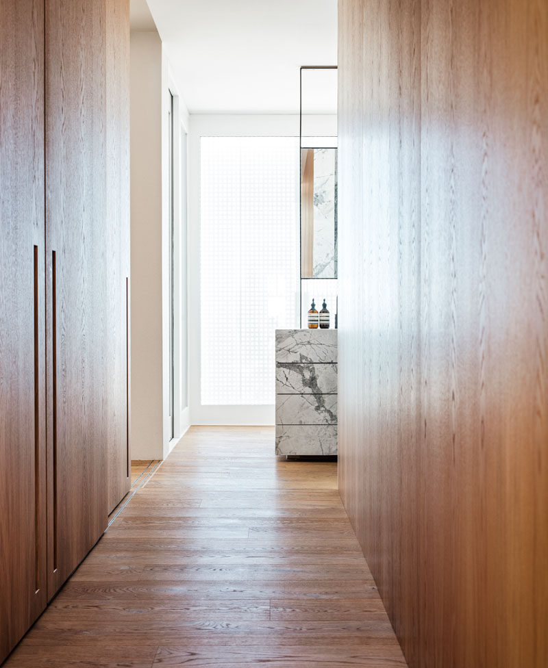 This modern bathroom has a dressing area with floor-to-ceiling wood closets. #WoodClosets #ModernClosets