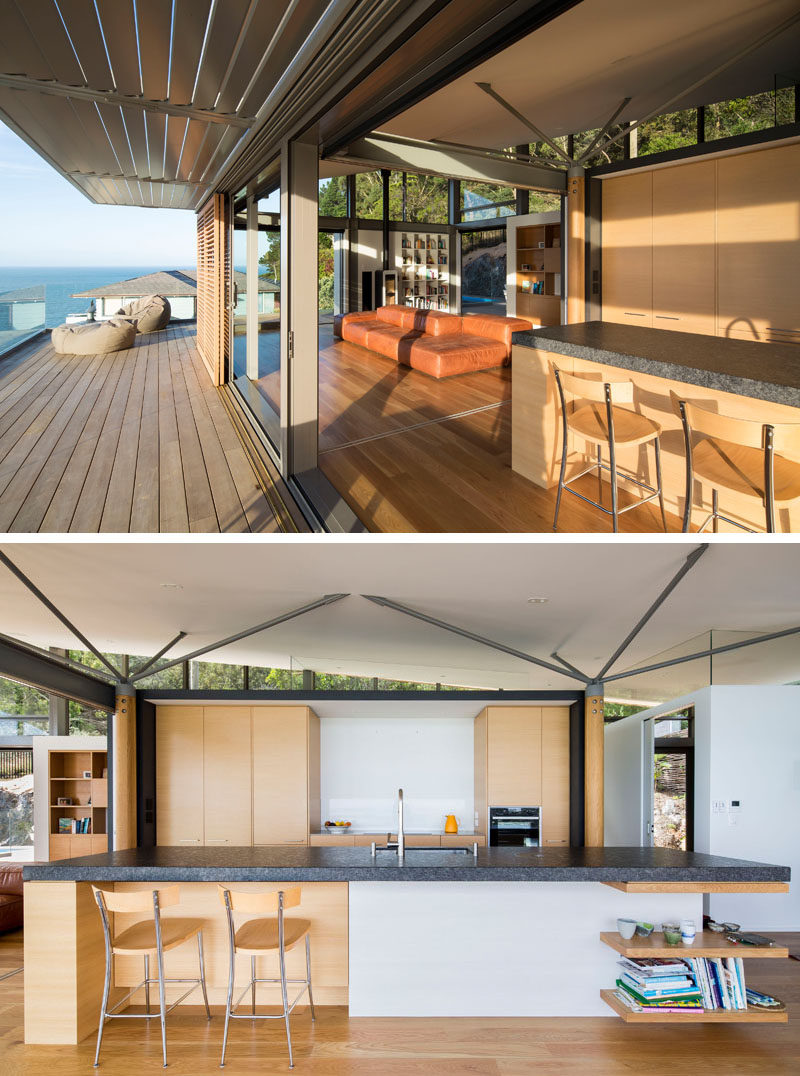 The top level of this modern house has an open plan kitchen, a dining and lounge area, a small study, and a toilet. In the kitchen, wood cabinets are combined with a thick dark countertop for a contemporary appearance. #ModernKitchen #KitchenDesign #OpenPlan
