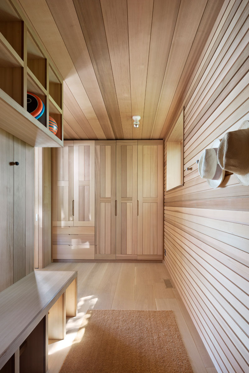 This wood-lined mudroom has floor-to-ceiling cabinets, hooks, and open shelving, providing plenty of space to store coats and shoes. #MudRoom