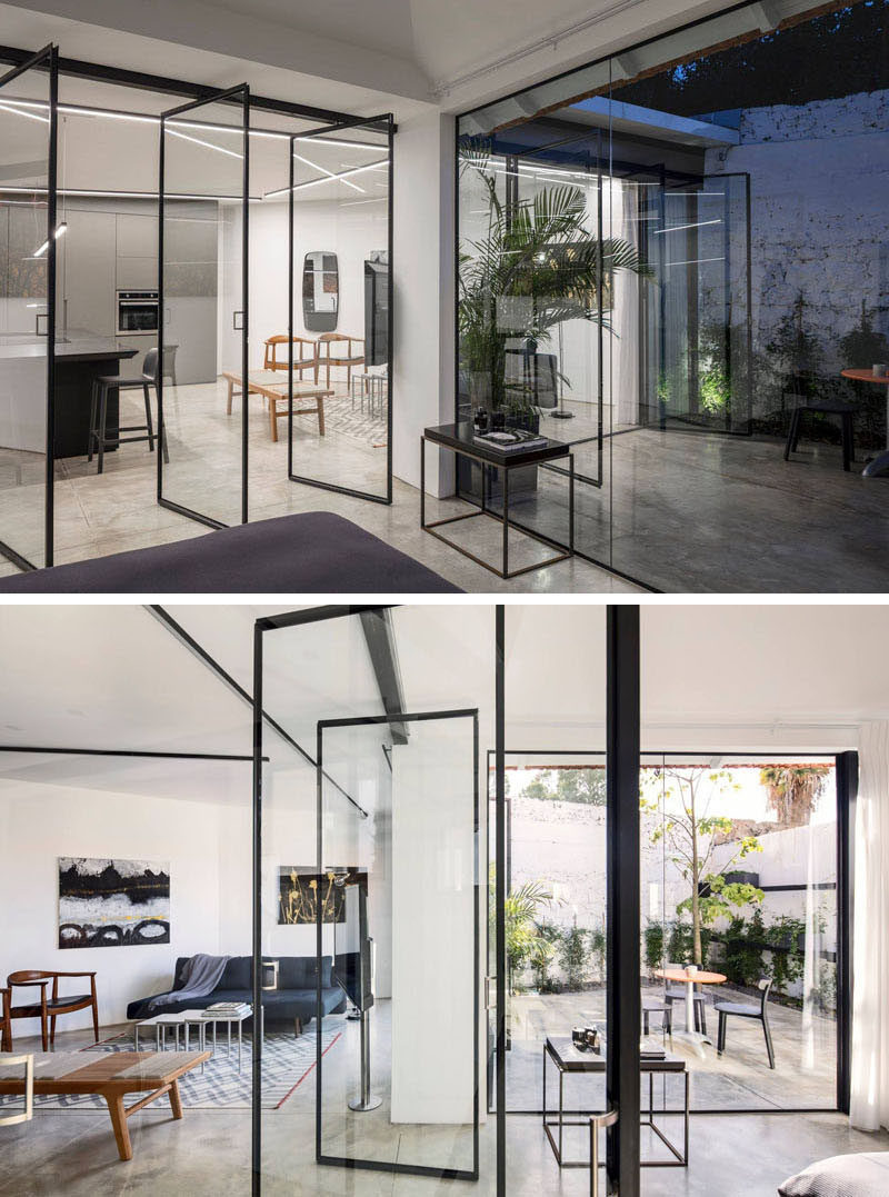 In this renovated home, Belgian style glass pivot windows between the kitchen and the bedroom were installed make the space feel large and open. #Doors #GlassWalls #Windows