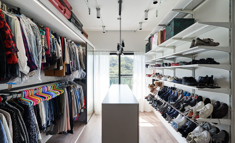 This modern walk-in closet makes use of the natural light from the floor-to-ceiling windows, and the white cabinetry and shelves provide ample space for clothes and shoes. #WalkInCloset #Closet #Storage