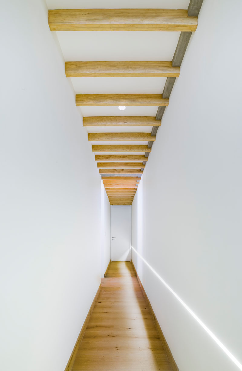This bright white and wood hallway leads to the bedrooms in a penthouse apartment. #WhiteHallway #WhiteAndWood #InteriorDesign