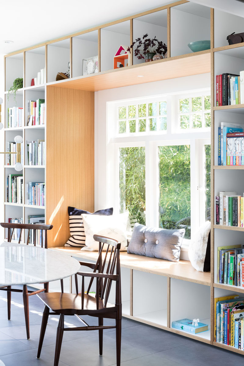 This wood framed built-in window seat is surrounded by open shelving, creating places to store books, decorative items, and toys. #WindowSeat #Shelving #Seating