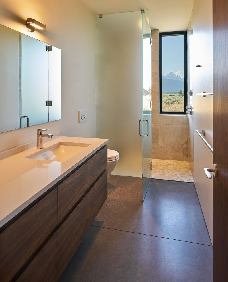 In this modern bathroom, there's a tall window in the shower, while a floor-to-ceiling frosted glass shower screen and door keeps the rest of the bathroom dry. #BathroomDesign #FrostedShowScreen #Window