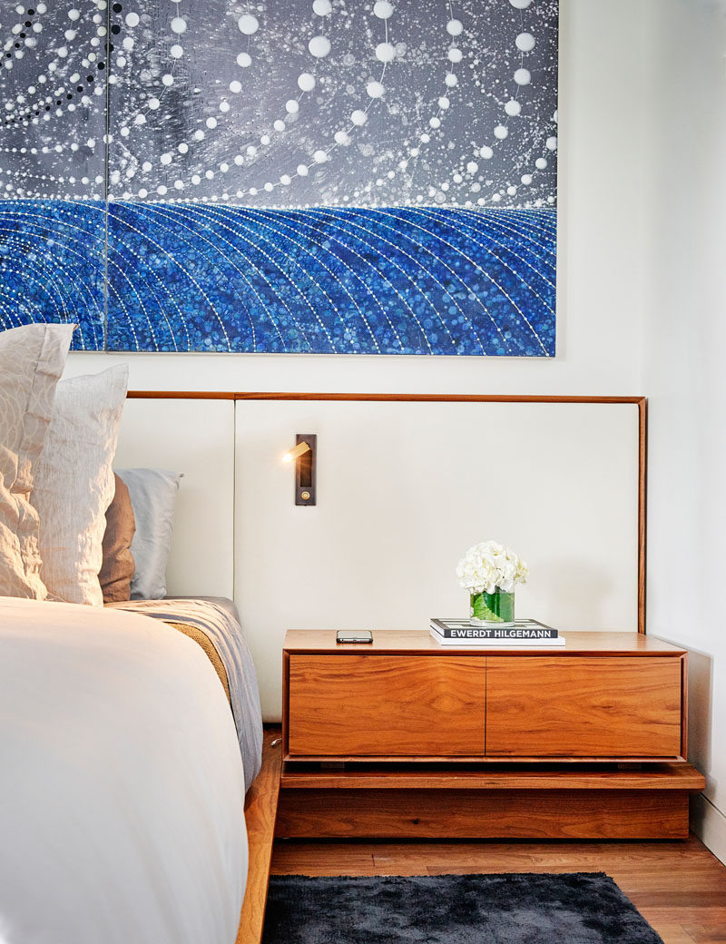 In this modern master bedroom, wood bedside tables are included as part of the wood bed frame. #MasterBedroom #BedroomDesign