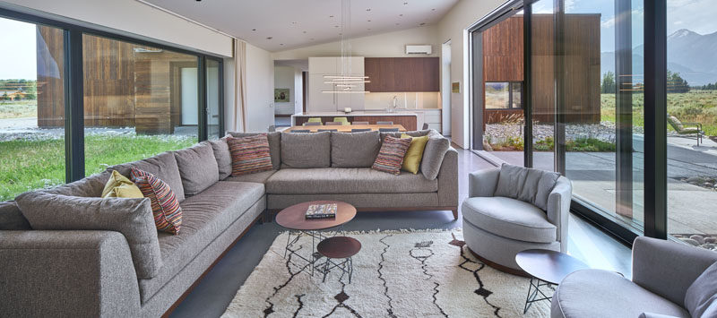Inside this modern house, the large windows (8ft x 10ft) perfectly frame the views and provide ample natural light to the social areas of the house, like the living room, while a 24 foot Zola lift and slide door opens up to a patio area. #ModernWindows #LargeWindows #LargeSlidingDoor #LivingRoom
