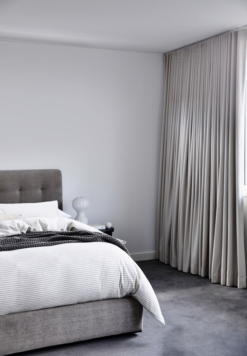 This master bedroom is minimalist in its design, with a grey color palette, and floor to ceiling light curtains to provide privacy. #ModernBedroom #BedroomDesign #MinimalistBedroom