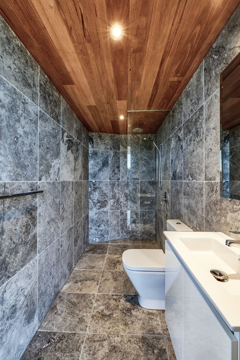 This modern bathroom with grey tiles and a walk-in shower with glass shower screen, is located within a pool cabana. #Bathroom #ModernBathroom