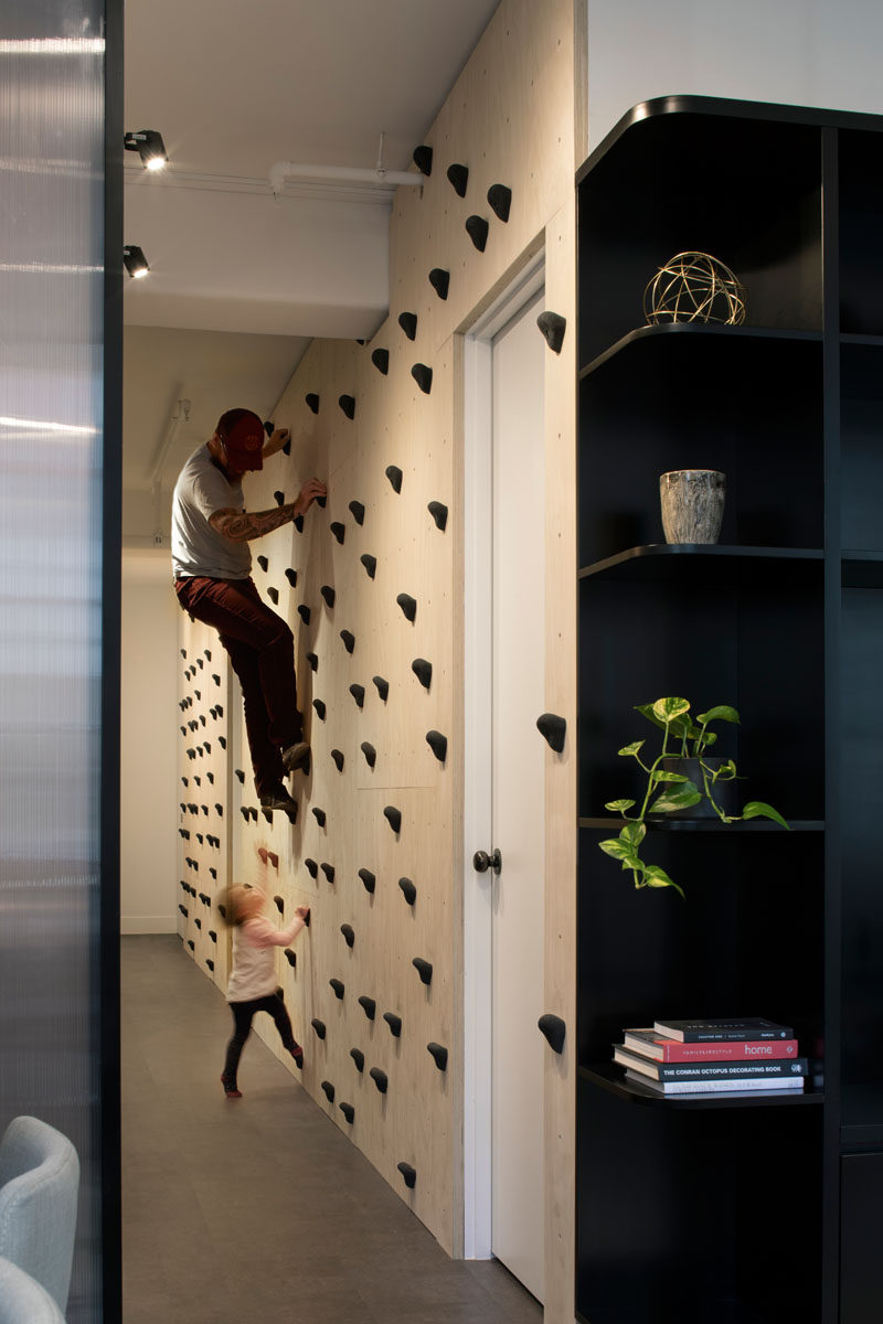 Upon entering this modern apartment, there's a plywood wall with rock climbing grips that lines the hallway. #RockclimbingWall #Rockclimbing #InteriorDesign