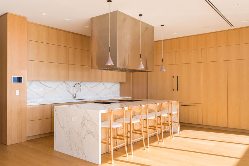 In this modern kitchen, light wood has been used for the cabinets, while the stone island ties in with the countertop and backsplash. #ModernWoodKitchen #KitchenDesign