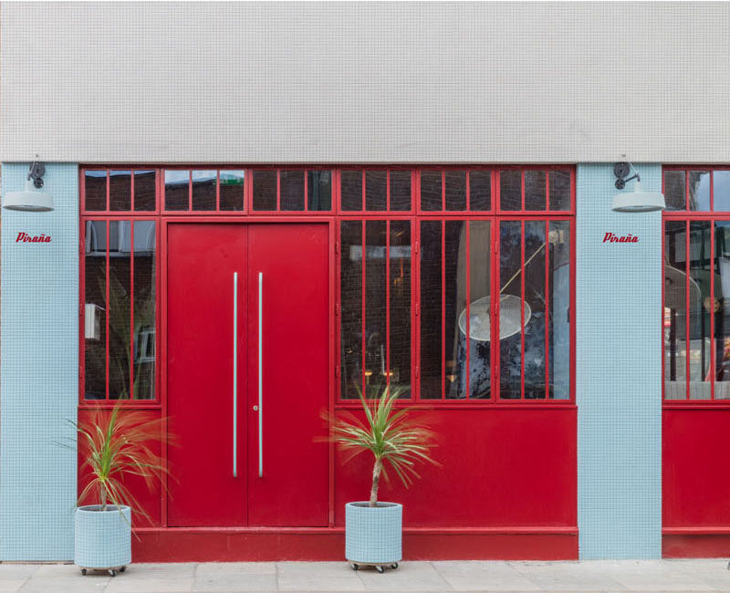 Sella Concept has recently completed the design and visual identity of Piraña, a South American-inspired bar and restaurant located in London, England. #RestaurantDesign #BarDesign #RedDoor