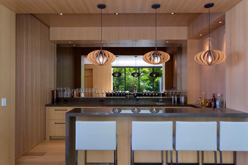 This modern home bar has a mirrored backsplash to make the room feel larger. #MirroredBacksplash #HomeBar