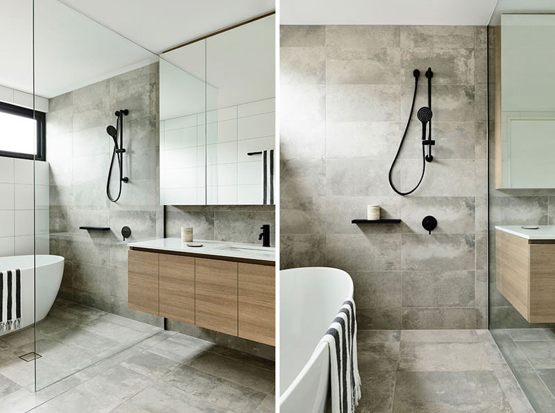 A glass partition separates the bath and shower from the dry areas of this bathroom, while allowing the natural light to filter through. #ModernBathroom #BathroomDesign