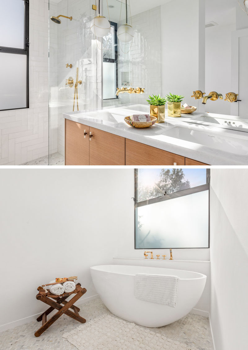 In this modern bathroom, a wood vanity with a marble top separates a freestanding bathtub from the walk-in shower. #ModernBathroom #BathroomDesign