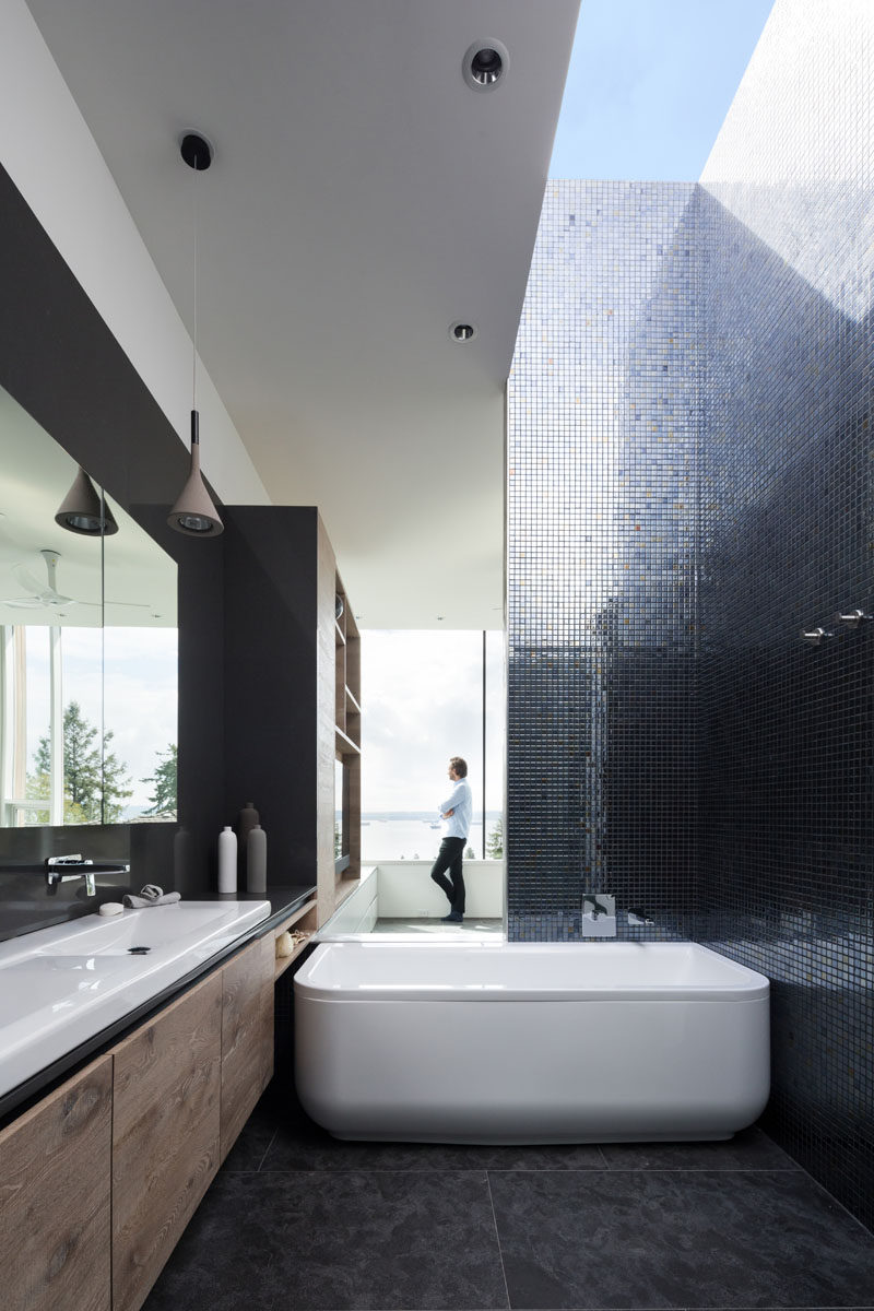 This modern ensuite bathroom has metallic tiles that reflect the natural light from the skylight, and a bathtub that when used, has a view through the bedroom and to the water views in the distance. #ModernBathroom #MetallicTiles #Skylight