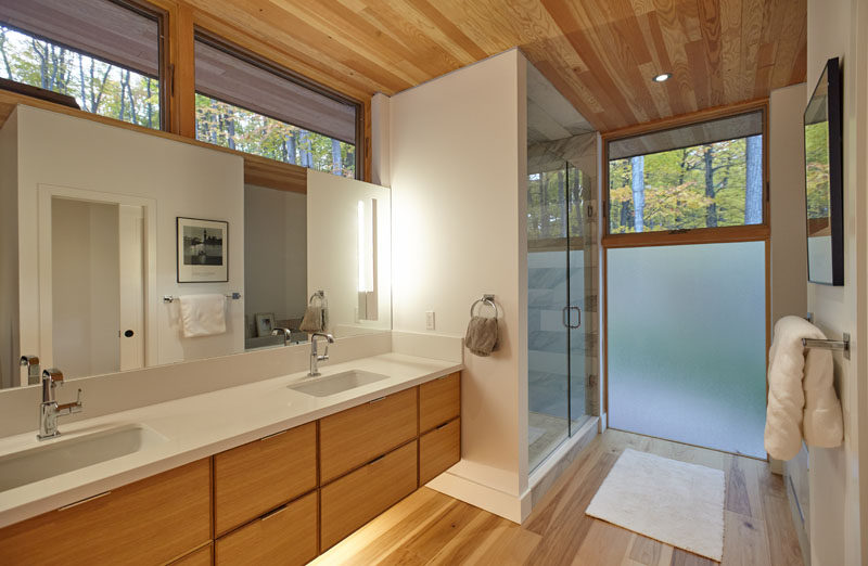 In this contemporary bathroom, a double sink wood vanity with a white countertop sits beside a walk-in shower. A frosted window provides privacy, but at the same time, still lets the natural light through. #BathroomDesign #ContemporaryBathroom #FrostedWindow