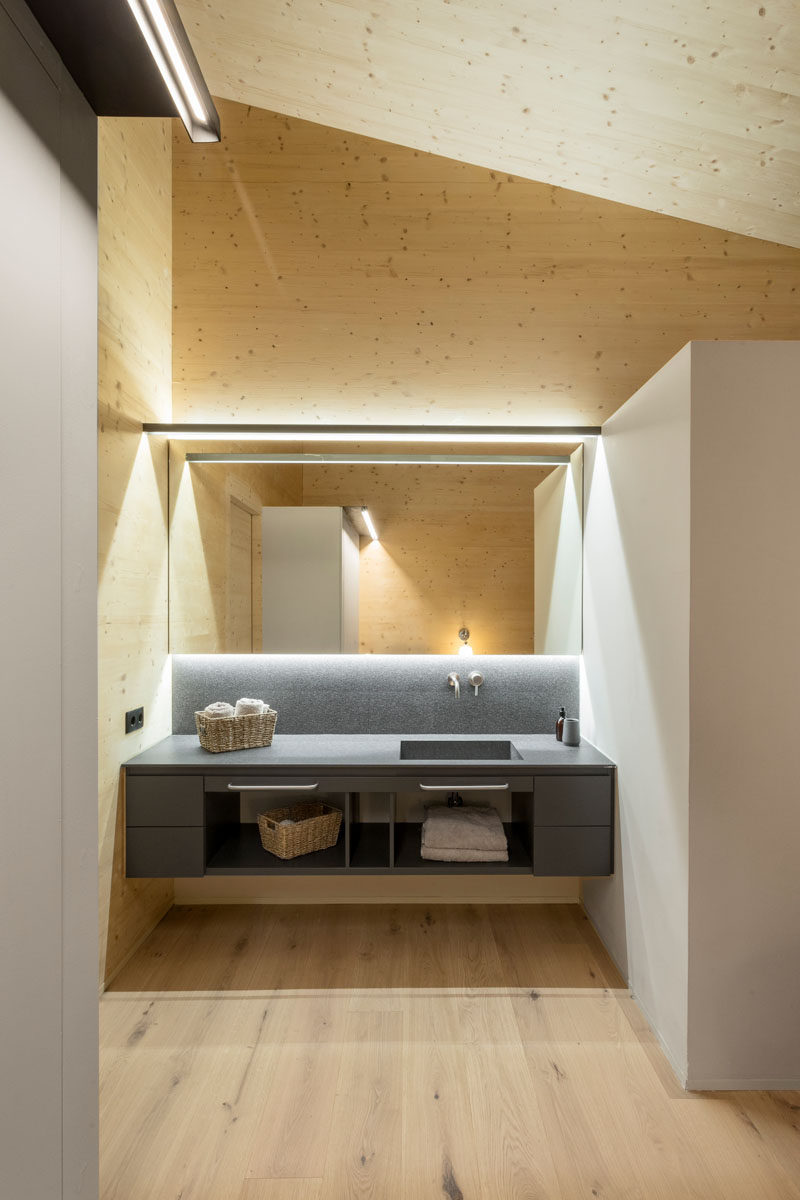 In this modern bathroom, grey cabinetry stands out against the wood walls and ceiling, while a backlit mirror and minimalist lighting highlight the vanity. #ModernBathroom #Lighting #BathroomDesign