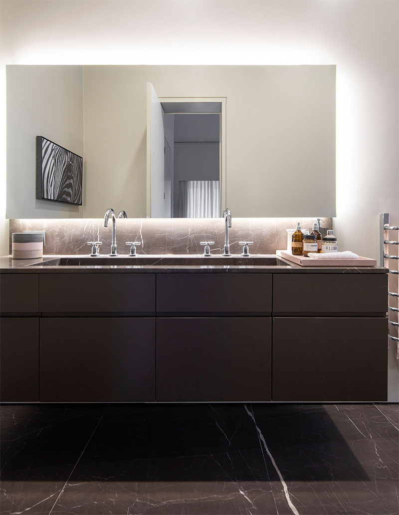 In this modern bathroom, a trough sink vanity with two faucets sits below a backlit mirror. #ModernBathroom #BathroomDesign #BacklitMirror