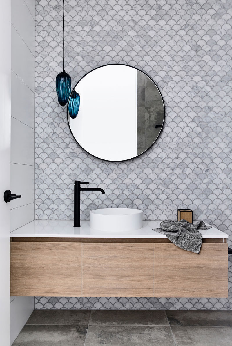 In this modern bathroom, fish scale tiles (also known as scalloped or fan tiles) have been used to create a decorative accent wall, while the blue light fixture adds a pop of color. #ModernBathroom #FishScaleTiles #ScallopTiles #FanTiles