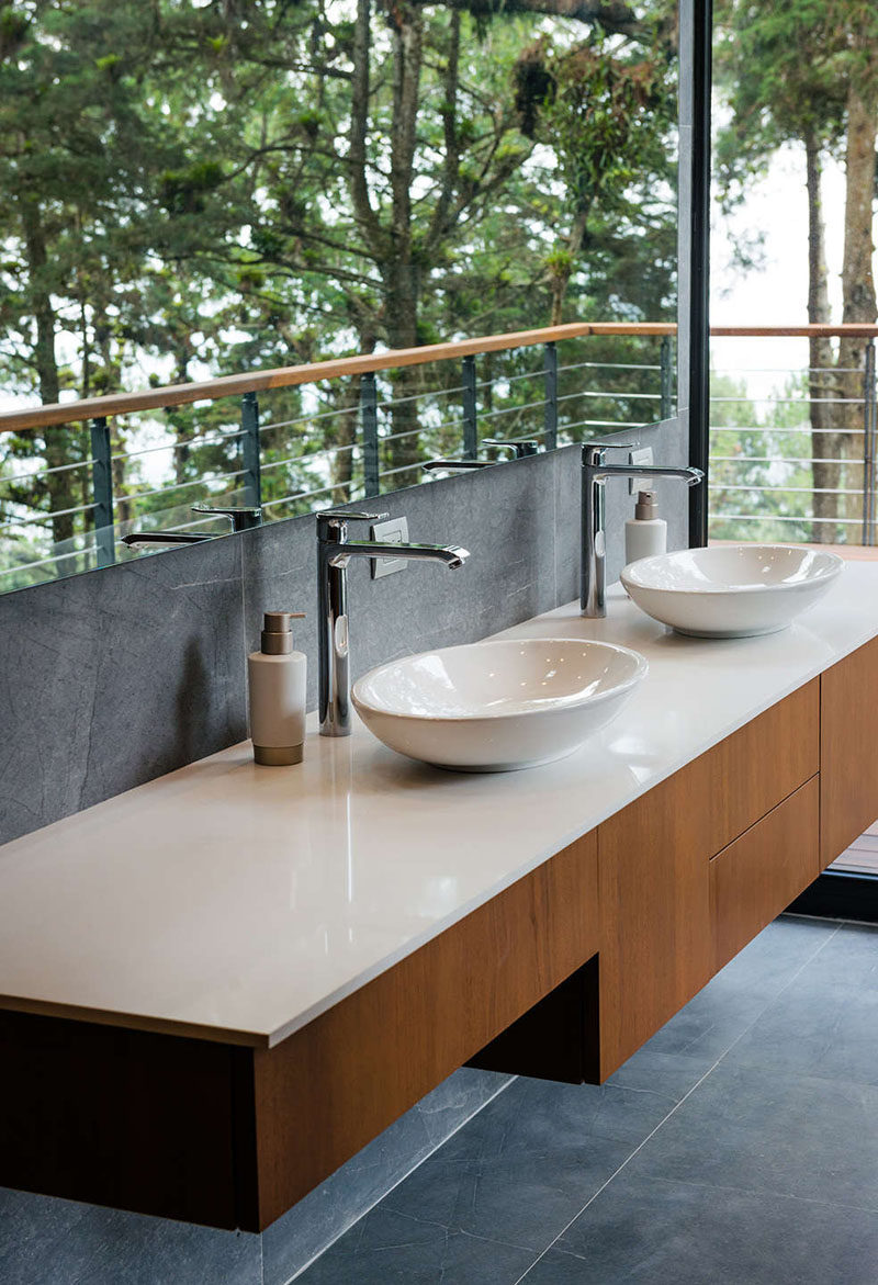 This modern bathroom has a large mirror that reflects the views from the window, and a floating wood vanity with a white countertop. #Bathroom #VanityDesign