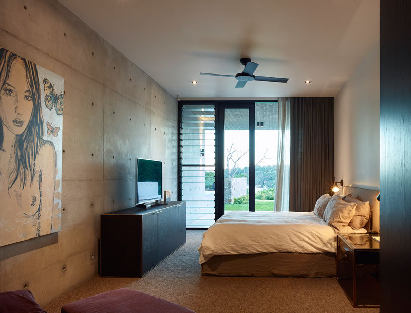 In this bedroom, a concrete wall has been paired with white smooth walls for a modern appearance. #ModernBedroom