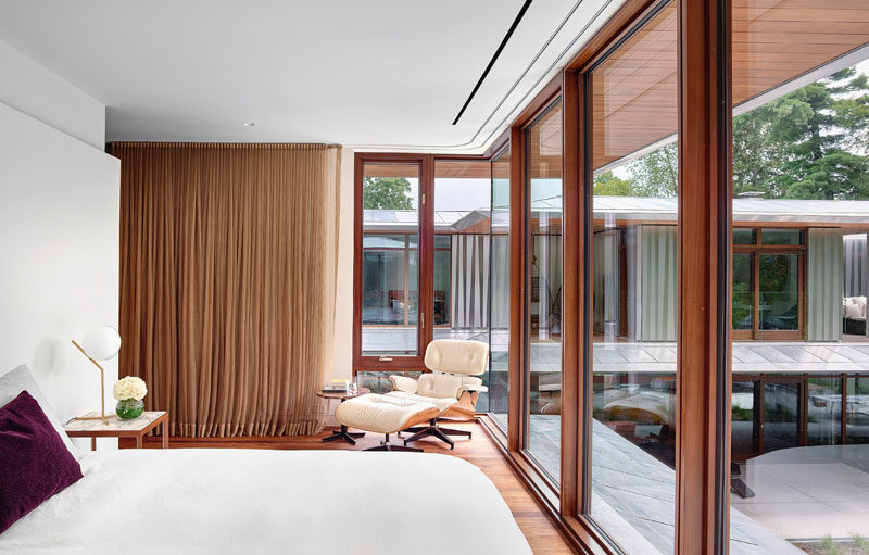This modern guest bedroom features floor-to-ceiling windows that provide a view of the top floor of the main house and the pool below. #GuestBedroom #Windows