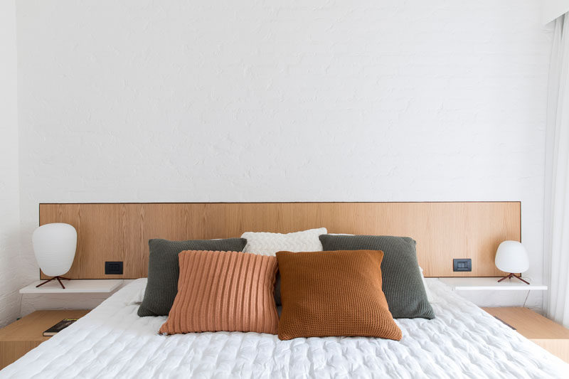 In this modern master bedroom, a wood headboard breaks up the white wall. #MasterBedroom #BedroomDesign #WoodHeadboard