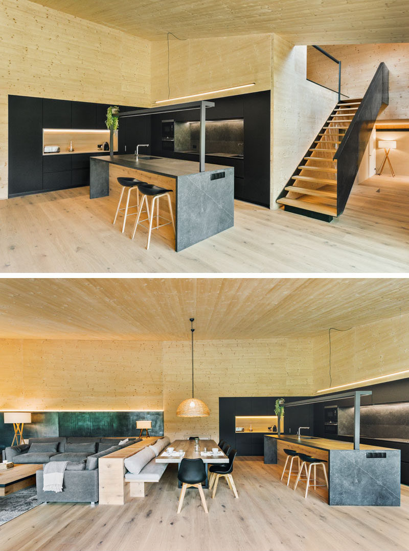 In this modern kitchen, the black cabinets complement the iron stairs, while a grey kitchen island adds a lighter touch. A pony wall separates the dining area and the living room, and provides a backrest for the bench. #BlackKitchen #PonyWall #DiningRoom #LivingRoom #OpenPlanInterior