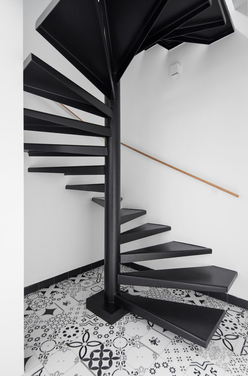 This modern two-floor apartment has black steel spiral stairs connect the different levels. #ModernStairs #BlackSpiralStairs