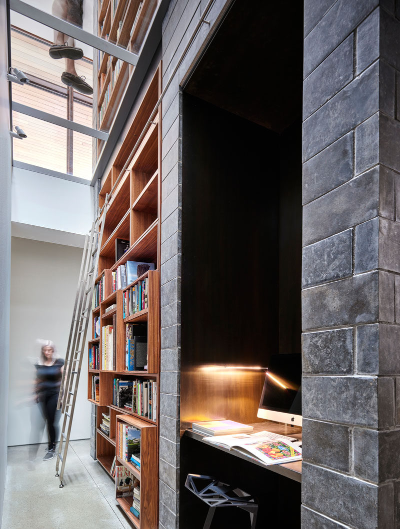 This modern house has a library with a built-in wood bookshelf, and an alcove with a desk and computer. #Bookshelf #BuiltInBookshelf